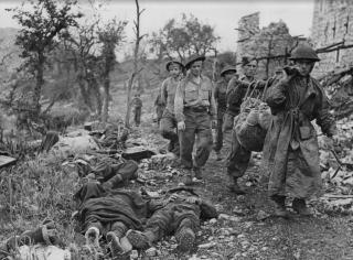 montecassino_Soldati alleati portano un compagno morto dalle macerie di Monte Cassino