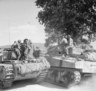 A Sherman tank passes a Churchill carrying infantry during 46th Division's assault on the Gothic Line, 2 September 1944