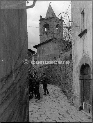 febb 1945 soldati in strada cutigliano pistoia un gruppo di 3 soldati riuniti in una stradina lastricata di pietre e una torre sullo sfondo la divisione di montagna
