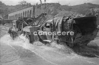Un camion Nuova Zelanda traino di un veicolo a fianco di un ponte demolito sul fiume zona Pisa 28 Luglio 1944