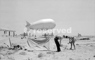 Personnel of a Beach Balloon Party erect their bivouacs on a Sicilian beach, while behind them a kite balloon is prepared for deployment_sicilia word war