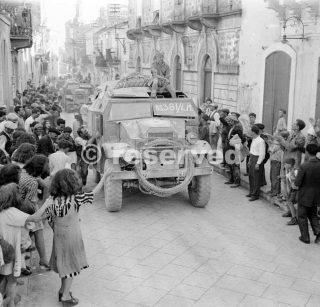 Quad trattori di artiglieria e 25pdrs di 51 Divisione Highland sono allietate da folle al loro ingresso Militello 15 Luglio 1943_sicilia word war