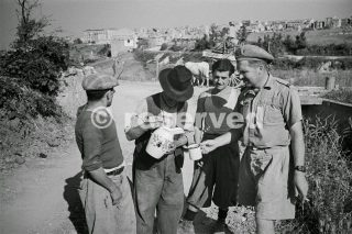 Civilians outside Orsogna Italy giving a drink of wine to a New Zealand soldier 16 June 1944_foto di guerra