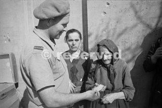 Un soldato Nuova Zelanda dà un pezzo di cioccolato a donna anziana che è tornata alla città italiana in rovina Orsogna_foto di guerra