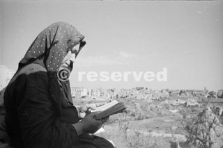 Una contadina italiana leggendo la sua Bibbia con le rovine di Orsogna sullo sfondo Fotografia scattata intorno al 16 giugno 1944_foto di guerra