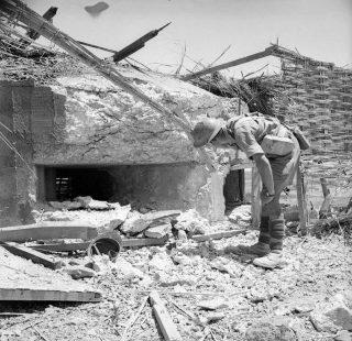 luglio 1943 Un soldato britannico ispeziona un fortino italiano catturato nella zona di Pachino sicacusa_sicilia