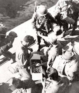 Napoli Uomini che ricevono CARTUCCE DI ANIDRIDE CARBONICA per i loro salvagente prima di salire a bordo delle navi per invasione