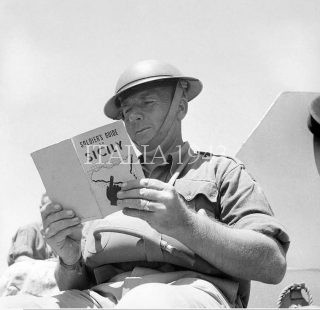 British soldier reads up on Sicily the target for the next Allied invasion July 1943