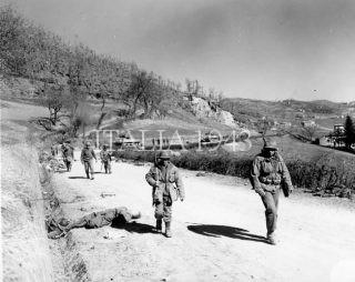 10a truppa di montagna, accompagnata da veicoli corazzati passa tedeschi morti lungo una strada dell'Appennino settentrionale il 4 marzo 1945